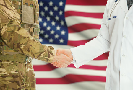 health service: Soldier in uniform and doctor shaking hands with national flag on background - United States