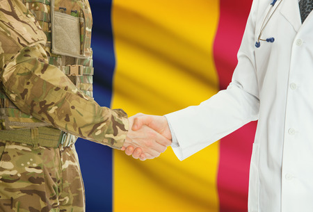 chadian: Soldier in uniform and doctor shaking hands with national flag on background - Chad