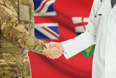 american hero: Soldier in uniform and doctor shaking hands with Canadian provincies and territories flags on background - Ontario Stock Photo