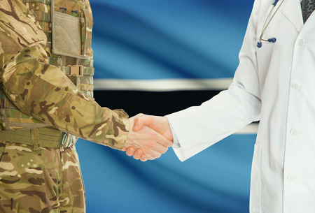 botswanan: Soldier in uniform and doctor shaking hands with national flag on background - Botswana