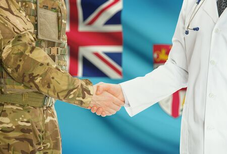fijian: Soldier in uniform and doctor shaking hands with national flag on background - Fiji Stock Photo