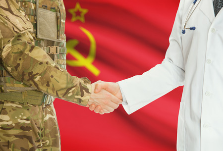 soviet flag: Soldier in uniform and doctor shaking hands with national flag on background - USSR - Soviet Union