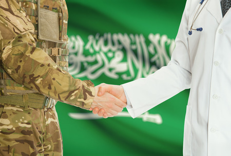 soldiers: Soldier in uniform and doctor shaking hands with national flag on background - Saudi Arabia