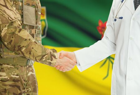 american hero: Soldier in uniform and doctor shaking hands with Canadian provincies and territories flags on background - Saskatchewan Stock Photo