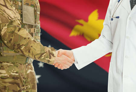 papua new guinea: Soldier in uniform and doctor shaking hands with national flag on background - Papua New Guinea