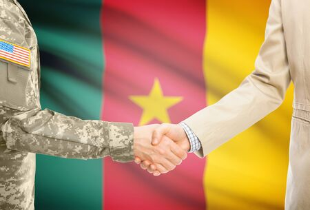cameroonian: American soldier in uniform and civil man in suit shaking hands with national flag on background - Cameroon