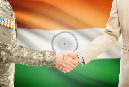 American soldier in uniform and civil man in suit shaking hands with national flag on background - India