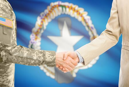 mariana: American soldier in uniform and civil man in suit shaking hands with national flag on background - Northern Mariana Islands