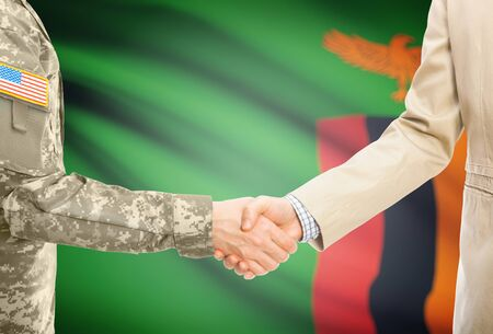 zambian: American soldier in uniform and civil man in suit shaking hands with national flag on background - Zambia Stock Photo