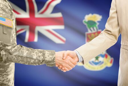 cayman islands: American soldier in uniform and civil man in suit shaking hands with national flag on background - Cayman Islands