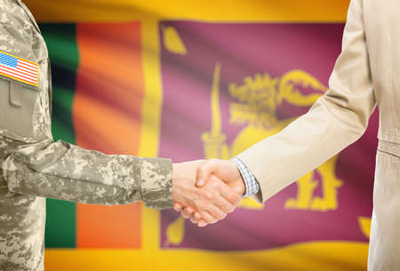 sri lankan flag: American soldier in uniform and civil man in suit shaking hands with national flag on background - Sri Lanka
