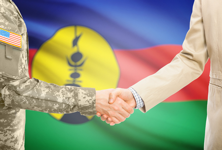 new caledonia: American soldier in uniform and civil man in suit shaking hands with national flag on background - New Caledonia