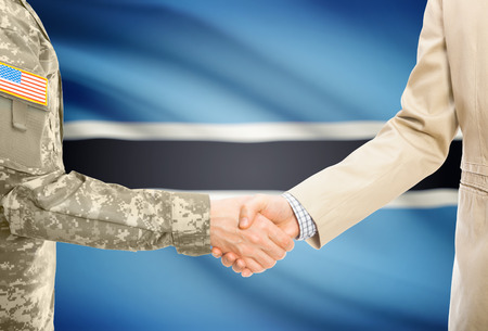 botswanan: American soldier in uniform and civil man in suit shaking hands with national flag on background - Botswana