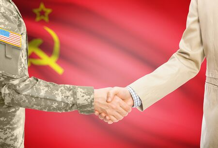 soviet flag: American soldier in uniform and civil man in suit shaking hands with national flag on background - USSR - Soviet Union