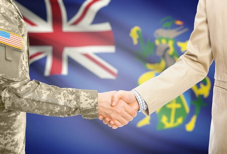 pitcairn: American soldier in uniform and civil man in suit shaking hands with national flag on background - Pitcairn Islands Stock Photo