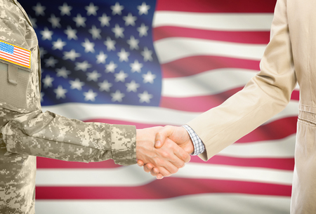 American soldier in uniform and civil man in suit shaking hands with national flag on background - United States Stock Photo