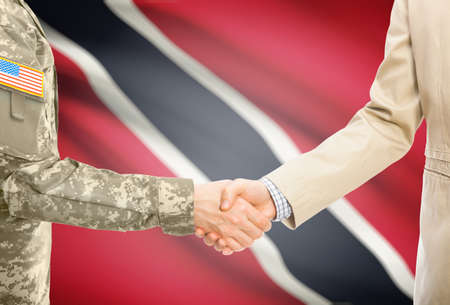 national flag trinidad and tobago: American soldier in uniform and civil man in suit shaking hands with national flag on background - Trinidad and Tobago