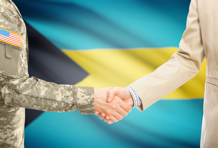bahamian: American soldier in uniform and civil man in suit shaking hands with national flag on background - Bahamas
