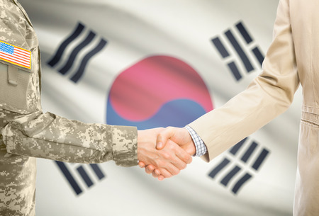 soldiers: American soldier in uniform and civil man in suit shaking hands with national flag on background - South Korea