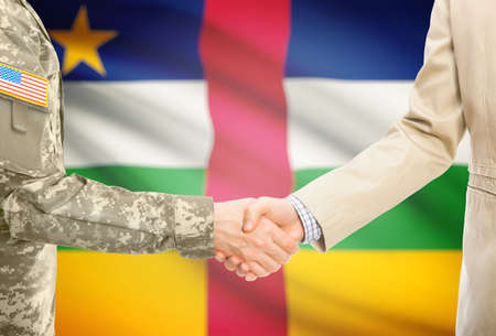 african warriors: American soldier in uniform and civil man in suit shaking hands with national flag on background - Central African Republic