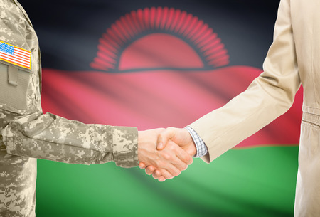 malawian: American soldier in uniform and civil man in suit shaking hands with national flag on background - Malawi Stock Photo