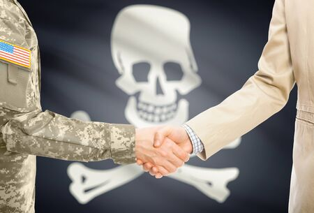 jolly roger: American soldier in uniform and civil man in suit shaking hands with flag on background - Jolly Roger - symbol of piracy