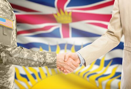 american states: American soldier in uniform and civil man in suit shaking hands with Canadian province flag on background - British Columbia Stock Photo