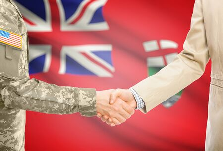 manitoba: American soldier in uniform and civil man in suit shaking hands with Canadian province flag on background - Manitoba Stock Photo