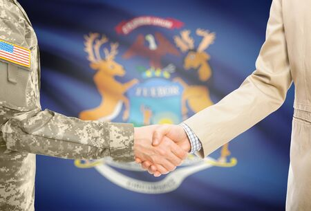 michigan flag: American soldier in uniform and civil man in suit shaking hands with USA state flag on background - Michigan
