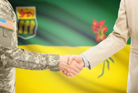 saskatchewan flag: American soldier in uniform and civil man in suit shaking hands with Canadian province flag on background - Saskatchewan Stock Photo