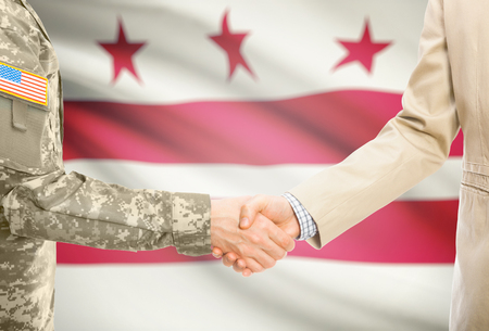 district of columbia: American soldier in uniform and civil man in suit shaking hands with USA state flag on background - District of Columbia