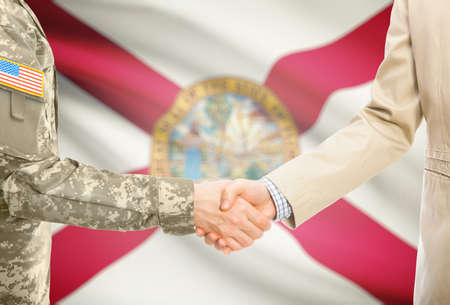 floridian: American soldier in uniform and civil man in suit shaking hands with USA state flag on background - Florida Stock Photo