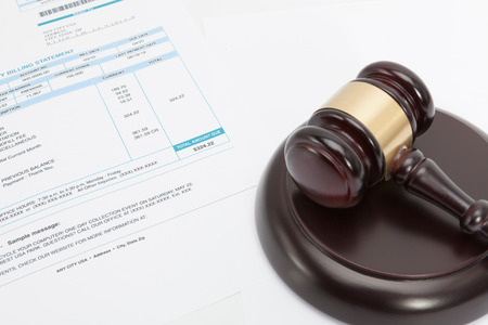 unpaid: Unpaid bill with wooden gavel over it Stock Photo
