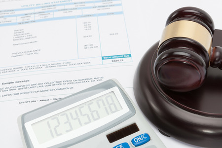 unpaid: Unpaid bill with wooden gavel and calculator over it