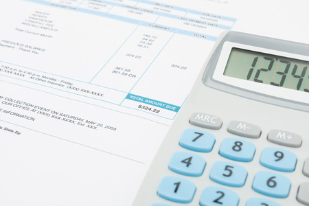 utility payments: Unpaid utility bill and calculator over it Stock Photo