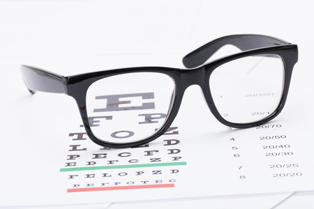 eye test: Table for eyesight test and glasses over it - studio shot