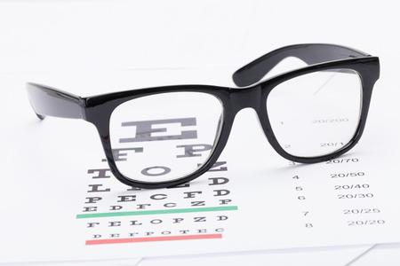 eye glasses: Table for eyesight test and glasses over it - studio shot