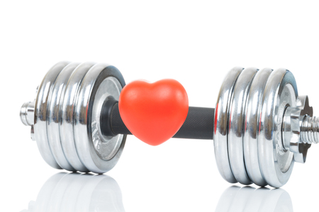chromed: Glossy chromed dumbbell with toy heart in front of it as symbol of healthy heart