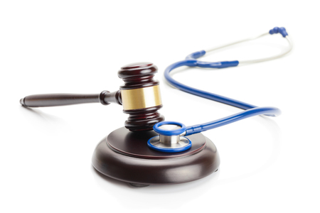 Close up studio shot of wooden judge gavel and stethoscope
