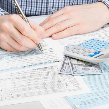 filling out: Close up studio shot of a male filling out 1040 US Tax Form