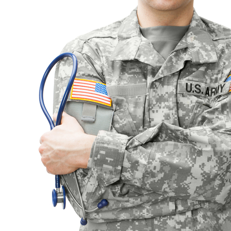 Close up studio shot of US Army doctor holding stethoscope near his shoulder Фото со стока