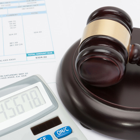 Unpaid bill with wooden gavel and calculator over it - close up studio shot