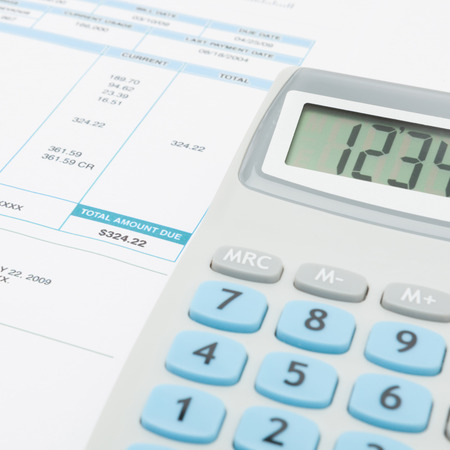unpaid: Unpaid utility bill and calculator over it - close up studio shot