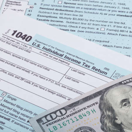 taxpayer: Close up shot of US 1040 Tax Form and dollars Stock Photo