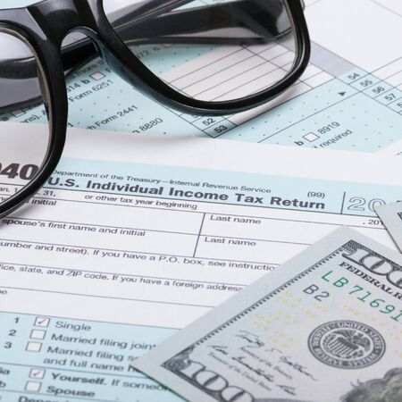 taxable income: Close up studio shot of US 1040 Tax Form with glasses and dollars over it Stock Photo