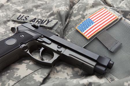 solders: Handgun over USA solders uniform with USA flag shoulder patch on it
