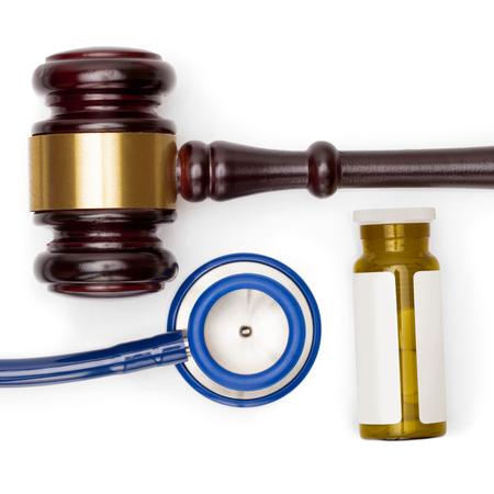 misbehavior: Wooden judge gavel, pills bottle and stethoscope on white backround - close up shot Stock Photo