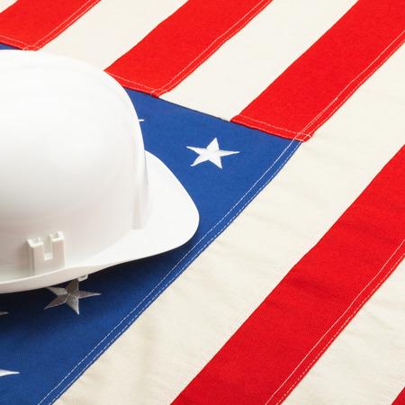 gewerkschaft: Close up Schuss eine weiße Farbe Bau Helm Verlegung über USA Flagge