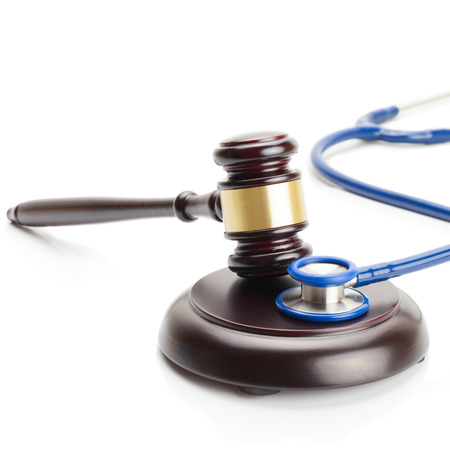 misbehavior: Close up studio shot of a wooden judge gavel and a stethoscope Stock Photo