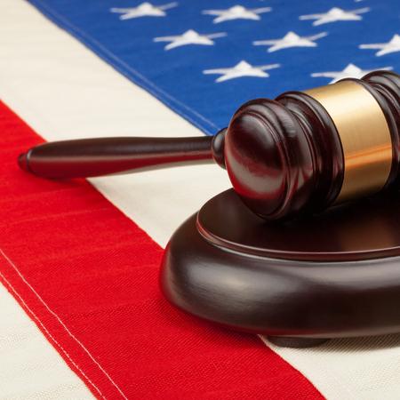 soundboard: Close up studio shot of a judge gavel and soundboard laying over USA flag